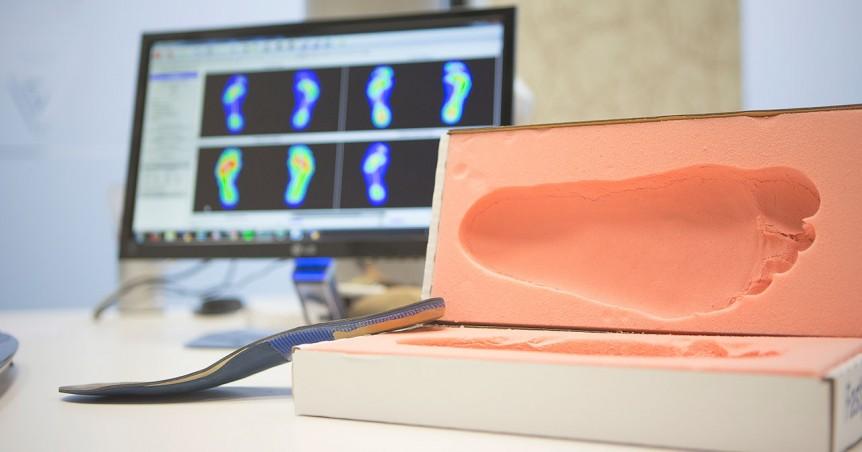 Una huella en un molde muestra la piada de un paciente, la pantalla del ordenador analiza la pisada para hacer plantillas adaptadas.