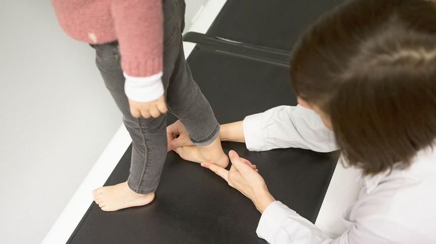 Una podóloga corrige la postura de los pies de una niña en la cinta de andar adaptada a niños.